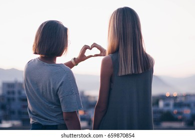 Two girls and heart shaped hands on the rooftop