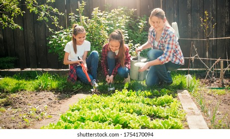 Two girls helping their mother working in garden and watering vegetables.