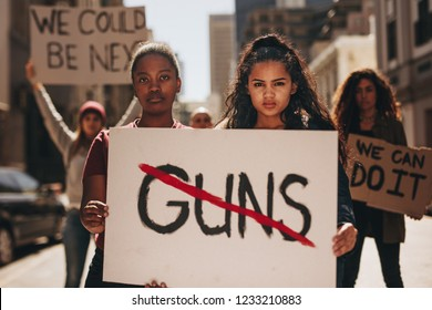 Two girls holding a banner with word guns strikethrough. Women holding sign that says not guns at a rally.