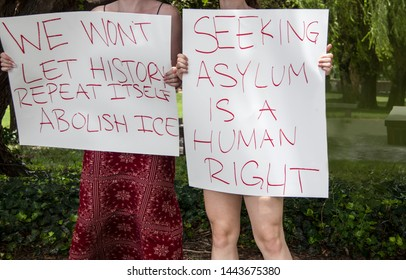 Two girls holding signs at immigration protest We wont let history repeat itself - abolish ice - asylum - cropped and selective focus - unrecognizable