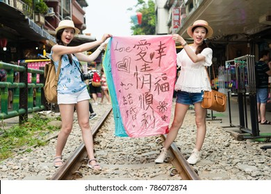 "two girls holding sky lanterns showing display to face to camera. Taiwan taipei travel concept. Translation on sky lanterns text ""hopes of happiness and good luck in love life in the future""."