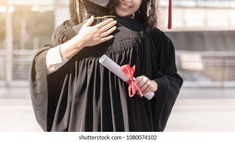 Two girls hug and congratulations each other at the university. They are graduates and hold diploma certificate. They are happy and in good mood.