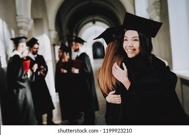 Two Girls Hug. Happiness. Asian Girl. Intelligence. Diploma. Standing. Corridor. University. Robes. Graduate. Good Mood. University. Cheerful. Celebration. Cap. Campus. Man. Knowledge. Mortar Board.