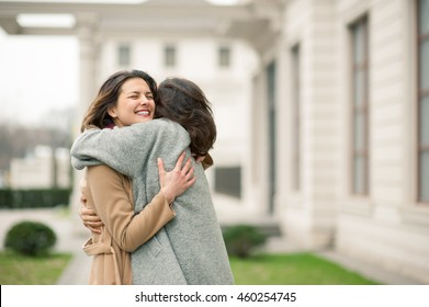 Two girls hug on the sidewalk. Feel joyfull and happy togather.
