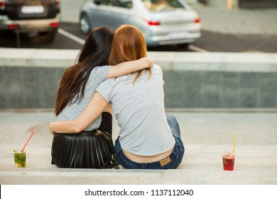 two girls hugging and drink cold cocktails, pretty friends, nice girlfriends walk around the city and drink lemonade. back view