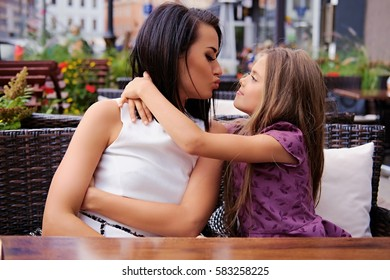 Two girls hugging at the table in an open air cafe.