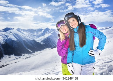 Two girls hugging in winter ski resort blue sky