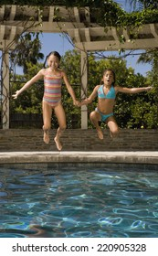 Two girls jumping into swimming pool