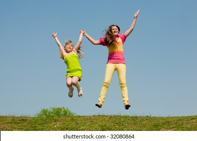 Two girls jumping on green meadow