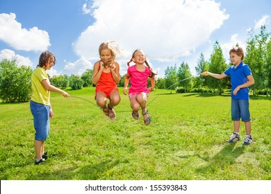 Two girls jumping over the rope with boys rotating the rope