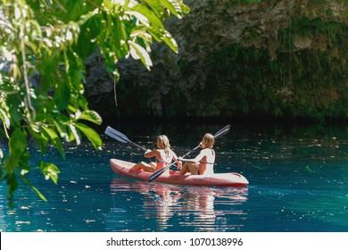 two girls kayaking on a blue lake, Laguna Dudu, Dominican Republic