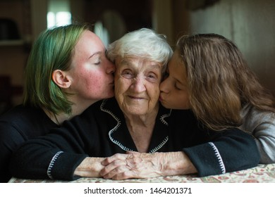 Two girls kissing their grandmother.