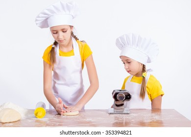 Two girls knead the dough, on a white background