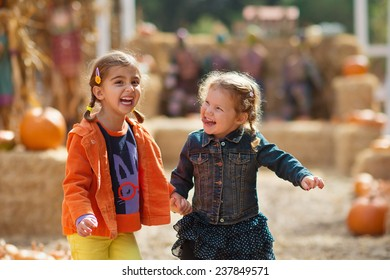 Two Girls Laughing at Pumpkin Patch