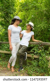 Two girls leaning by wooden fence in woodland setting in summer.
