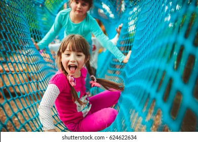 Two girls lie on blue rope tunnel