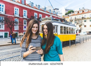 Two girls in Lisbon with the famous yellow tram on background. Young happy women looking at a smartphone in the city. Lifestyle and travel concepts.