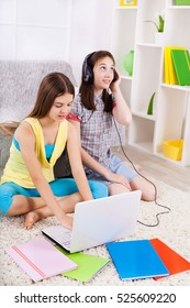 Two girls listening to music with headphones and choosing songs on laptop.