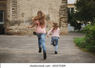 two girls with long hair running away