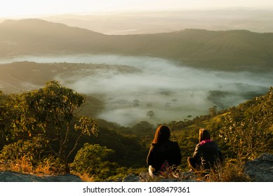 Two girls looking at the fog in the mountains at sunrise in Brazil