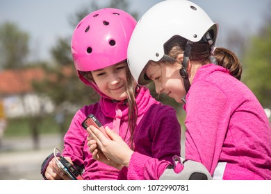 Two girls looking at smartphone.