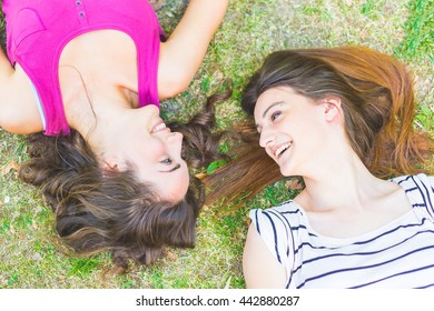 Two girls lying on the grass and laughing looking each other. One has curly hair and the other has straight hair, both brunette. Relaxation and friendship concepts.
