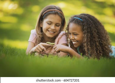 Two girls lying on the grass, one holding a green caterpillar on her finger,