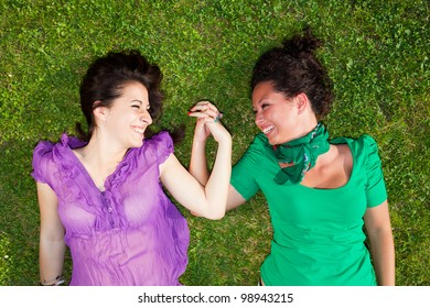 Two Girls Lying on the Grass and Holding Hands