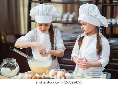 two girls make flour dough