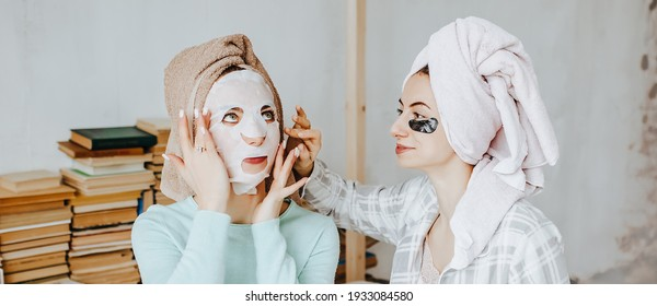 Two girls make masks and patches for the beauty of face and hair. Women take care of youthful skin. Girlfriends laugh, make faces and do beauty treatments at home with towels on their heads.