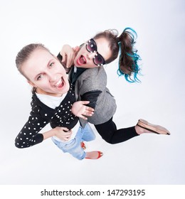 two girls making funny faces - isolated on bluish background