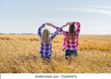 Two girls making the infinity sign in wheat field