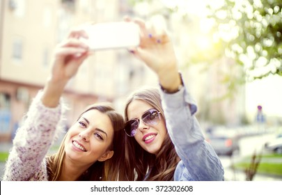 Two girls making self portrait.They both are with big smiles, highly enjoying the time spent together.