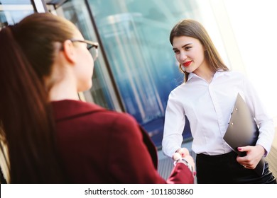 two girls managers smile and shake hands after signing a contract or a successful deal