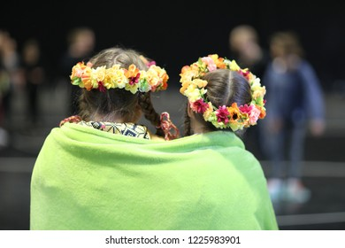 Two girls, members of the dance group, with braids and wreaths on her head, wrapped with a fleece blanket