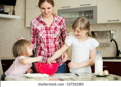 Two girls with mom cook in the kitchen