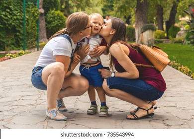 Two girls (mom) kiss their capricious little boy child in the park. Not a traditional family.