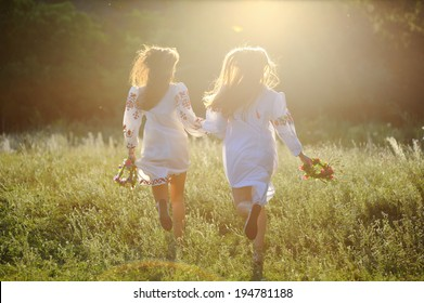 two girls in the national Ukrainian clothes with wreaths of flowers in their hands running over the grass