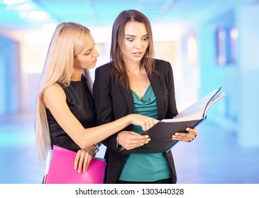 Two girls in the office with folders with papers in hand. Young women discuss office work. Blue empty hall on the background