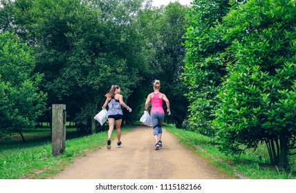 Two girls on back with garbage bags doing plogging