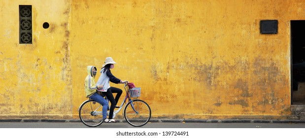 Two Girls on Bicycle with Old Wall in Vietnam