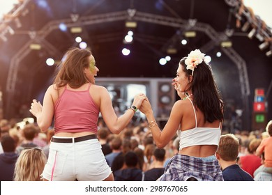Two girls on shoulders in the crowd at a music festival - Shutterstock ID 298767065
