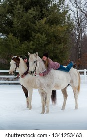 two girls on their horses bareback along white fence. Winter scene with snow