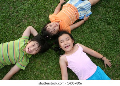 Two girls & one boy lying on the grass