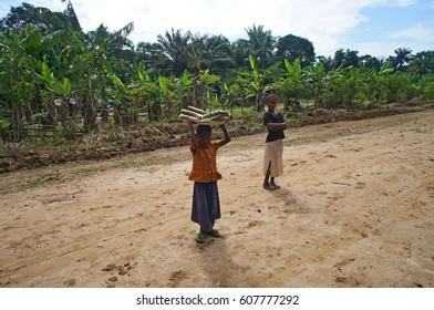 Two girls, one carrying kwanga (fermented manioc). Dongou, Likouala District, Republic of Congo (Congo Brazzaville), March 2014.