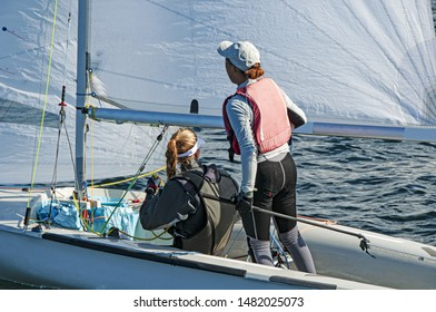 Two girls one standing other sitting sailing a racing skiff closeup outdoors on a sunny summers day. Teamwork by junior sailors racing on saltwater Lake Macquarie. Photo for commercial use.