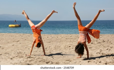 Two girls in orange clothes doing cartwheel on the beach