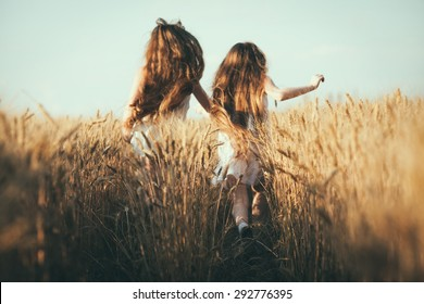 Two girls Outdoors raising hands in sunlight rays. Beautiful Teenage Model. Two girls in white dress running on the Field, Sun Light. Glow Sun. Free Happy Woman