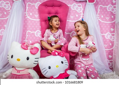 Two girls in pajamas and with toys Hello Kitty on a photo shoot. Girls in pajamas are laughing and having fun