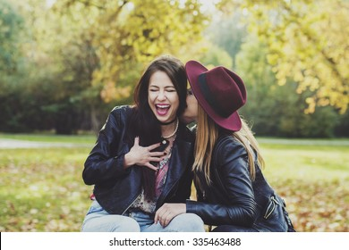 Two girls in a park on a bench laughing